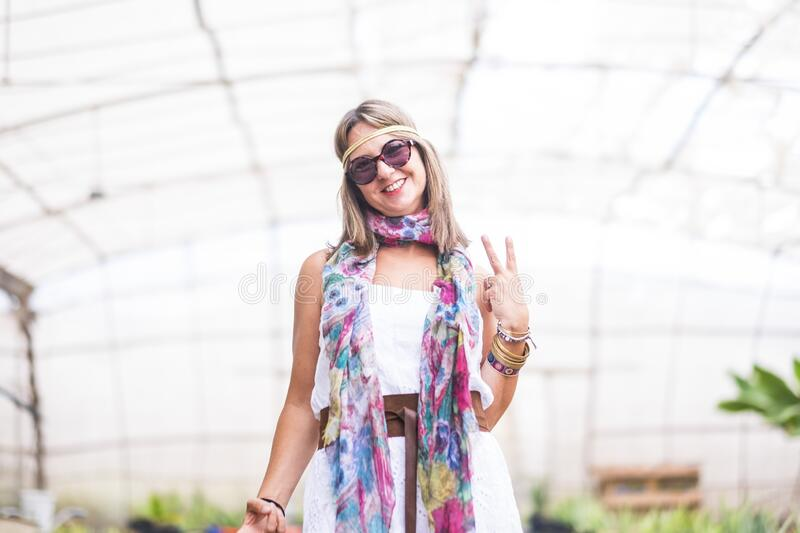Cheerful coloured hippy style free and smiling young blonde alernative woman with coloured clothes pose in front of the camera and royalty free stock photography