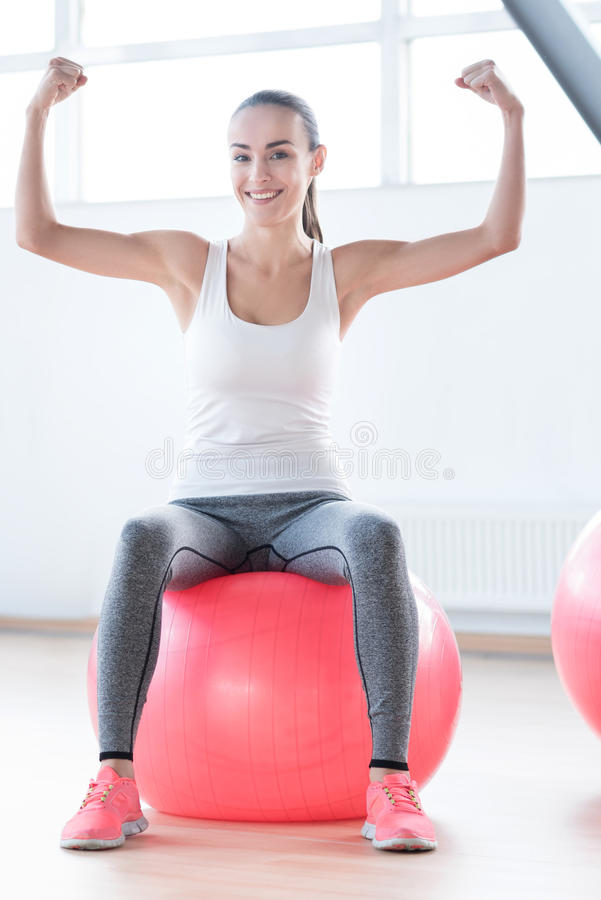 Cheerful confident woman showing her muscles stock photography