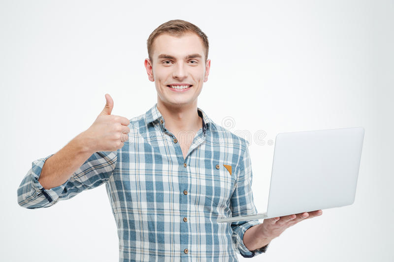 Cheerful confident young man holding laptop and showing thumbs up. Over white background royalty free stock image