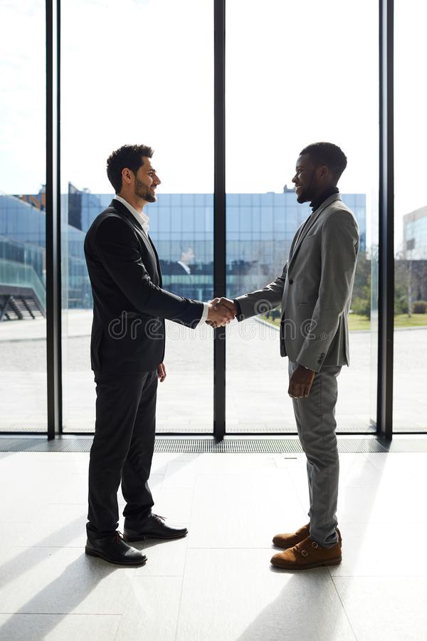 Welcoming business partner to company. Cheerful confident young mixed race manager in black suit welcoming business partner to company and shaking hands with him stock photo