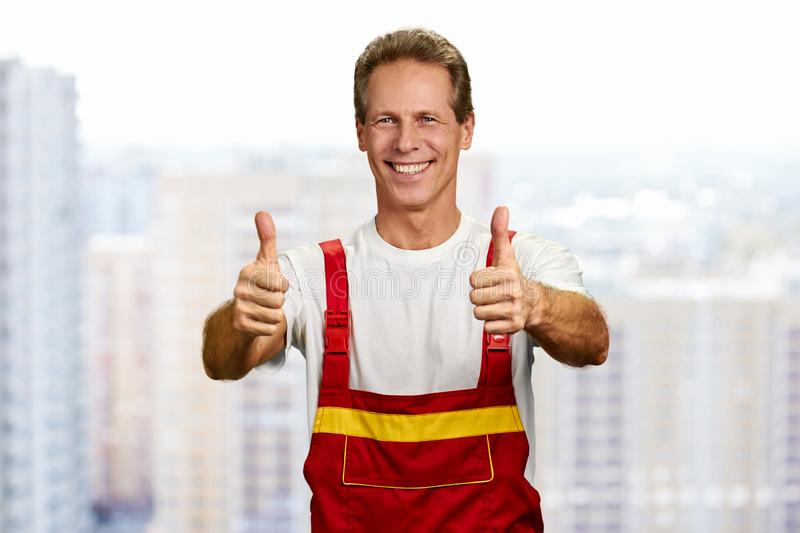 Cheerful construction worker showing two thumbs up. royalty free stock photos