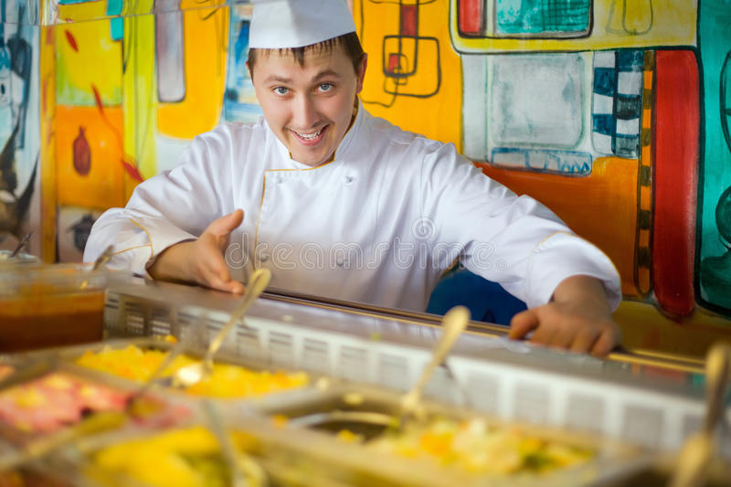 Cheerful cook in uniform near counter with meal royalty free stock photography