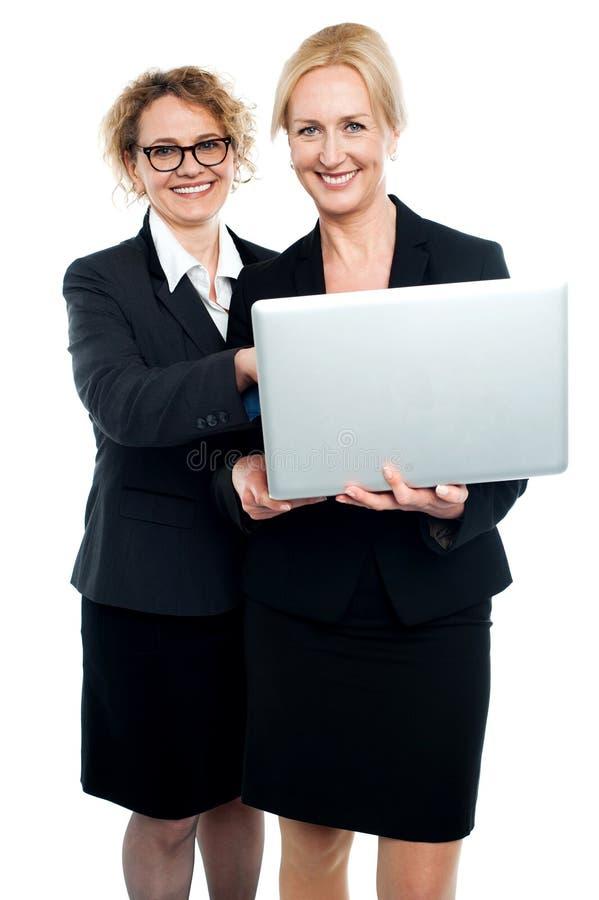Cheerful corporate ladies using laptop stock photos
