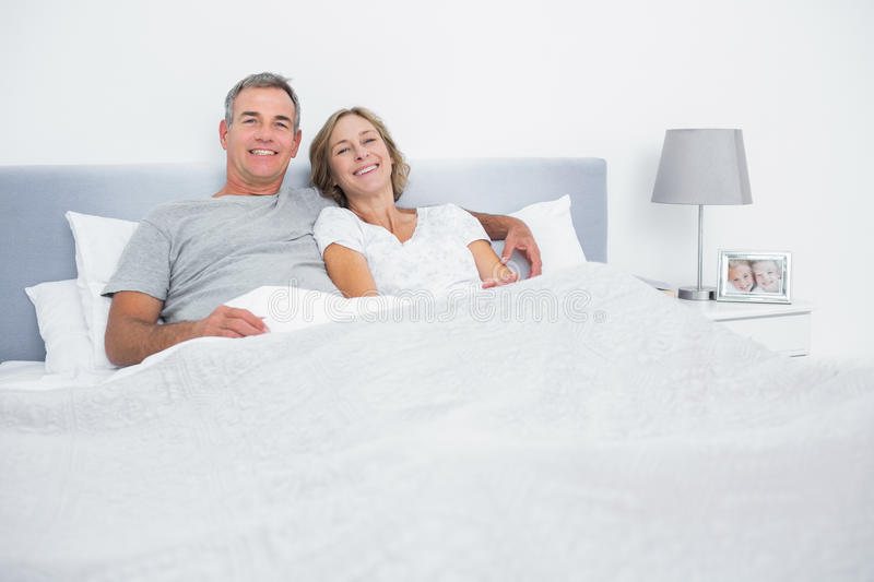 Cheerful couple cuddling in bed looking at camera