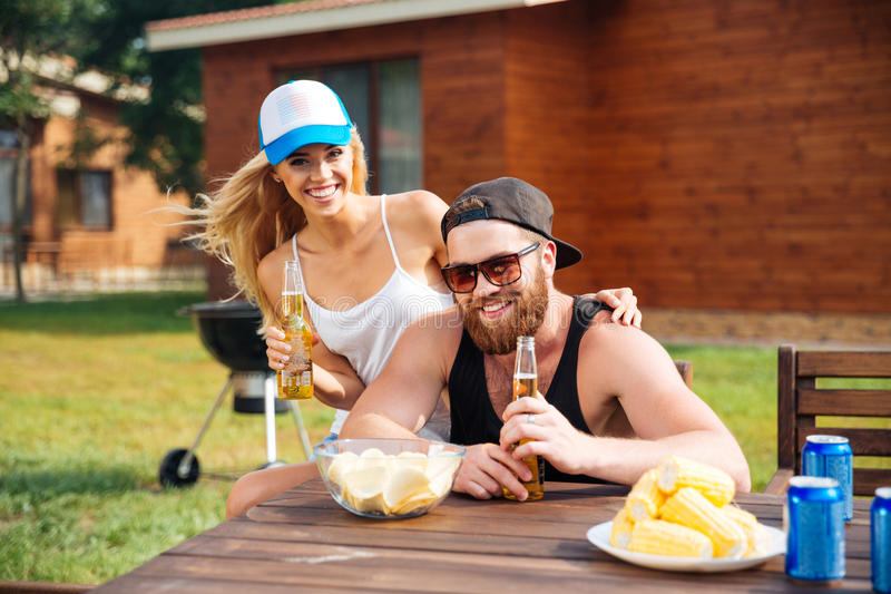 Cheerful couple eating and drinking beer outdoors at the table royalty free stock photos