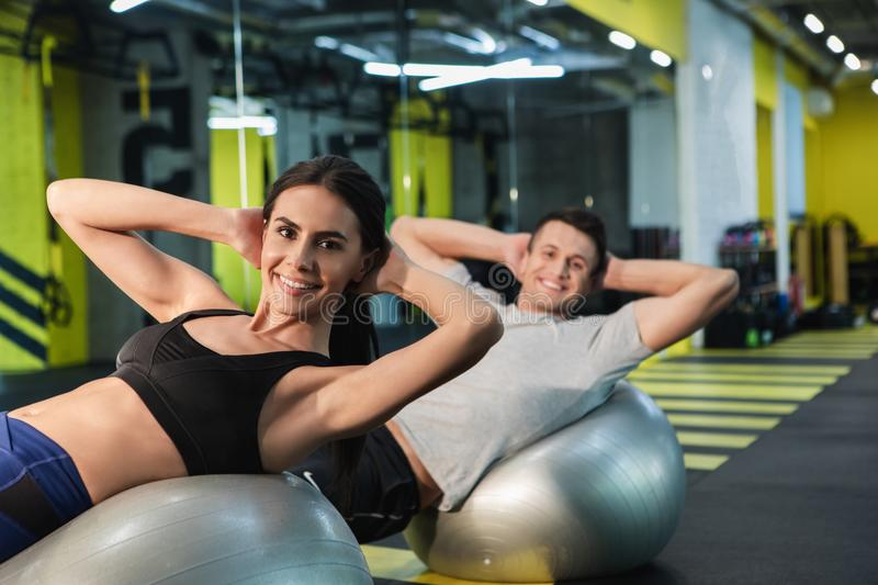 Cheerful couple is exercising abdomen with outfit in gym stock photo