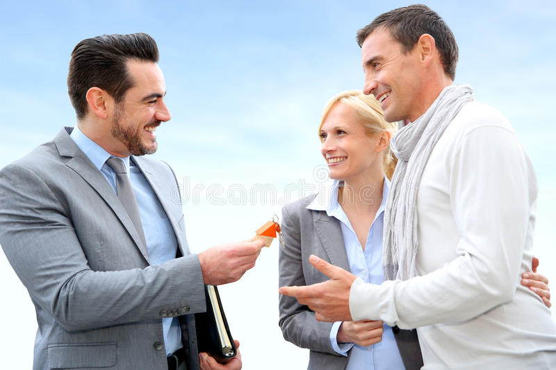 Cheerful couple getting home keys. Salesman giving home keys to property owners royalty free stock image