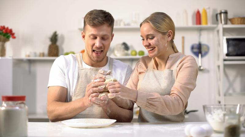 Cheerful couple having fun with dough at kitchen, romantic date for beloved royalty free stock photos