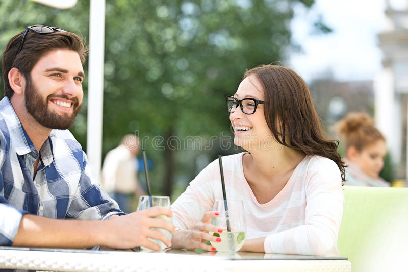 Cheerful couple having mojito at sidewalk cafe stock photo