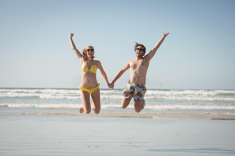 Cheerful couple holding hands while jumping at beach royalty free stock photo