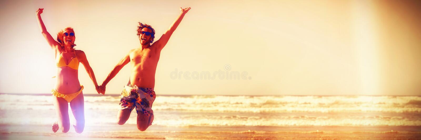 Cheerful couple holding hands while jumping at beach royalty free stock images