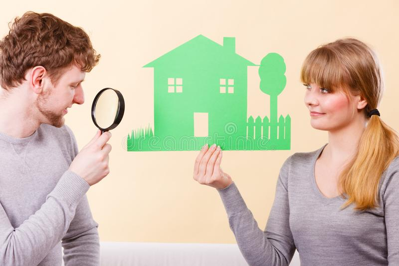 Cheerful couple with house. Home real estate credit mortgage concept. Cheerful couple with house. Young men and women holding building cutout and magnifying royalty free stock photos