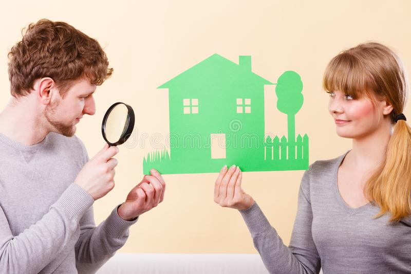 Cheerful couple with house. Home real estate credit mortgage concept. Cheerful couple with house. Young men and women holding building cutout and magnifying stock photography