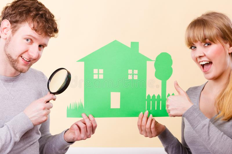 Cheerful couple with house. Home real estate credit mortgage concept. Cheerful couple with house. Young men and women holding building cutout and magnifying stock photos
