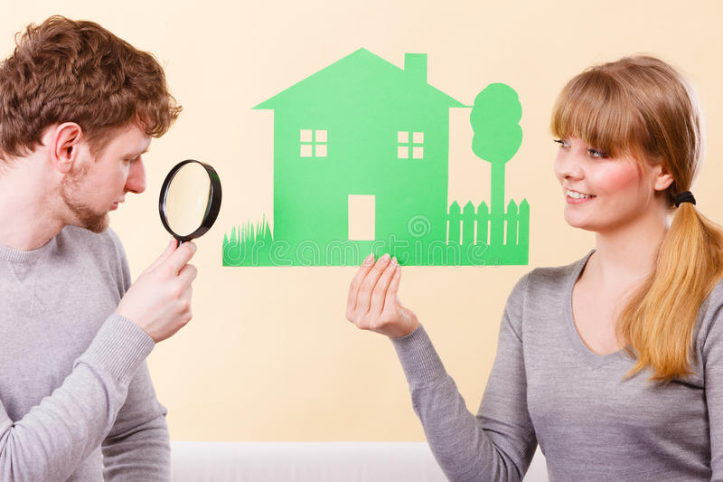 Cheerful couple with house. Home real estate credit mortgage concept. Cheerful couple with house. Young men and women holding building cutout and magnifying royalty free stock photo