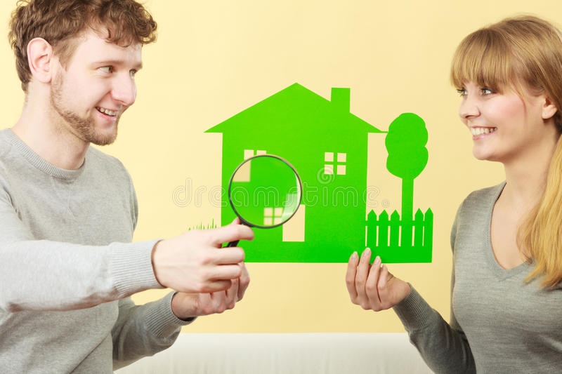 Cheerful couple with house. Home real estate credit mortgage concept. Cheerful couple with house. Young men and women holding building cutout and magnifying stock photo