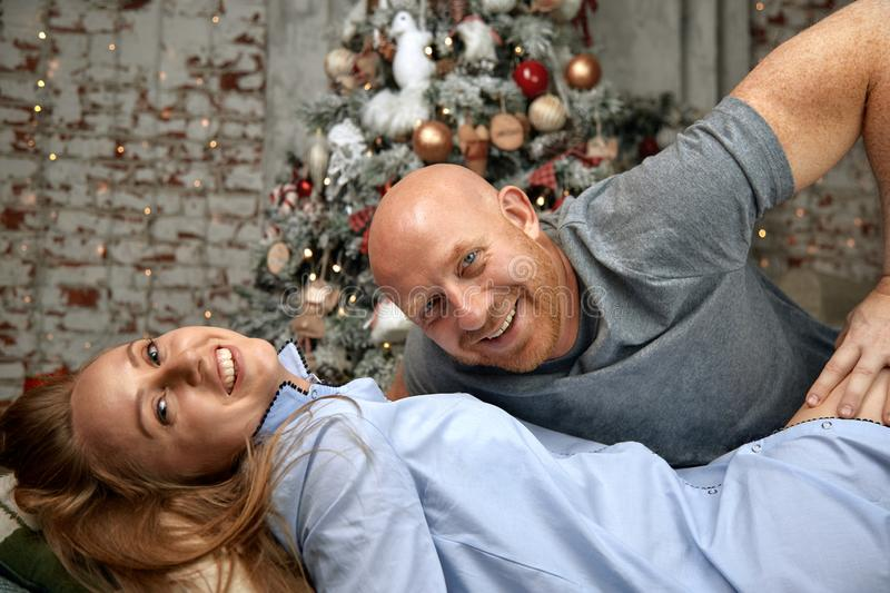 Cheerful couple hugging, enjoying together on Christmas Eve. Christmas concept in anticipation of a miracle, family. Marriage, young couple for the new year stock photos
