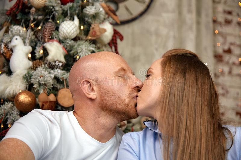 Cheerful couple hugging and kissing, enjoying together on Christmas Eve. Christmas concept in anticipation of a miracle. Cheerful couple hugging, enjoying royalty free stock images