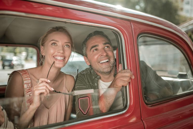 Cheerful couple looking out of the car window. stock photo