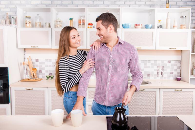 Cheerful couple in love making coffee in the kitchen stock images
