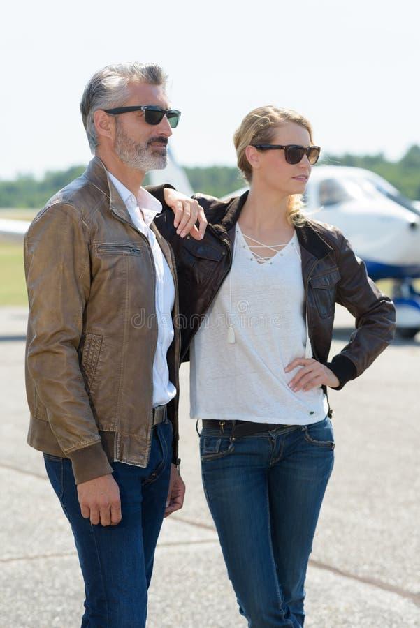 Cheerful couple near private plane stock photos