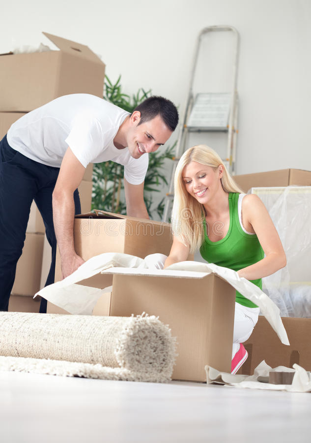 Cheerful couple in new home. Unpacking boxes stock photo