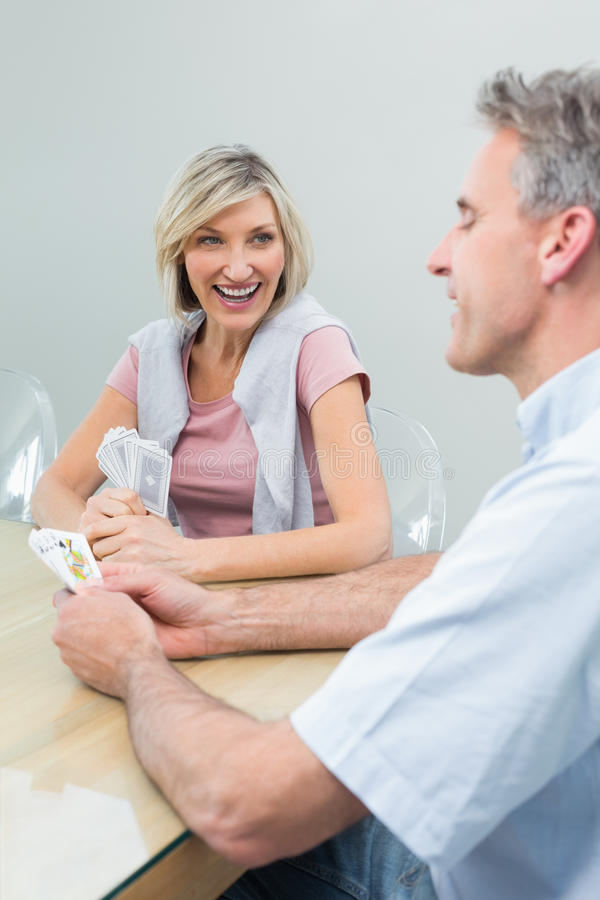 Cheerful couple playing cards at home stock image
