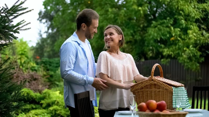 Cheerful couple preparing for picnic in country house, healthy food, well-being. Stock photo stock images