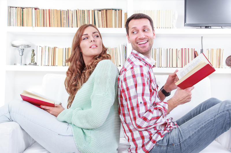 Cheerful couple reading a different books together. Reading a different books together. Cheerful young men and women reading different books together while royalty free stock image