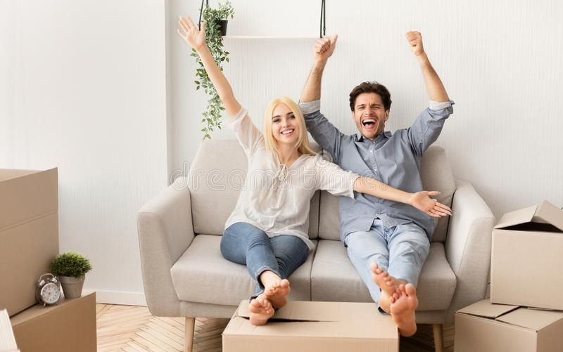 Cheerful Couple Relaxing On Sofa Celebrating Moving To New House royalty free stock photography