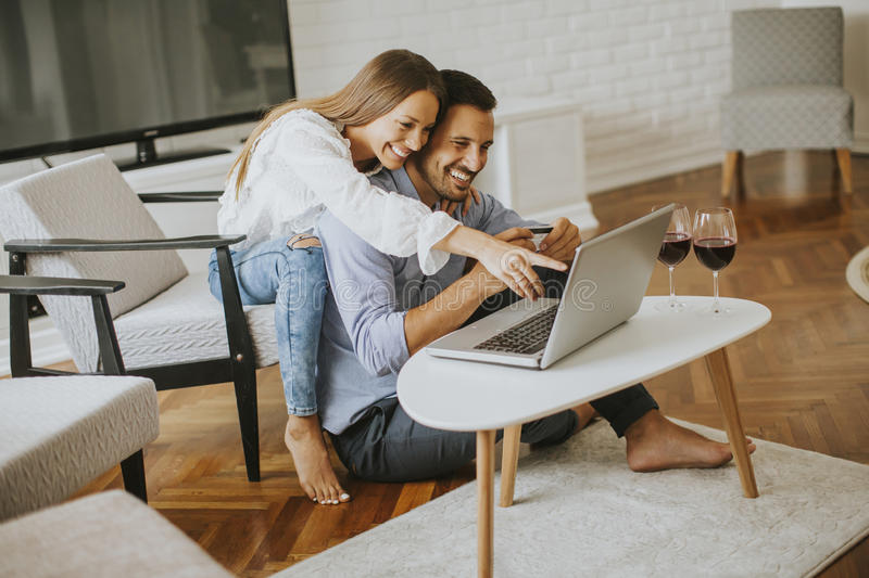 Cheerful couple searching internet on laptop at home stock photo
