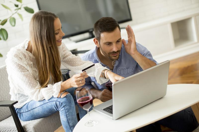Cheerful couple searching internet and shopping online stock photography