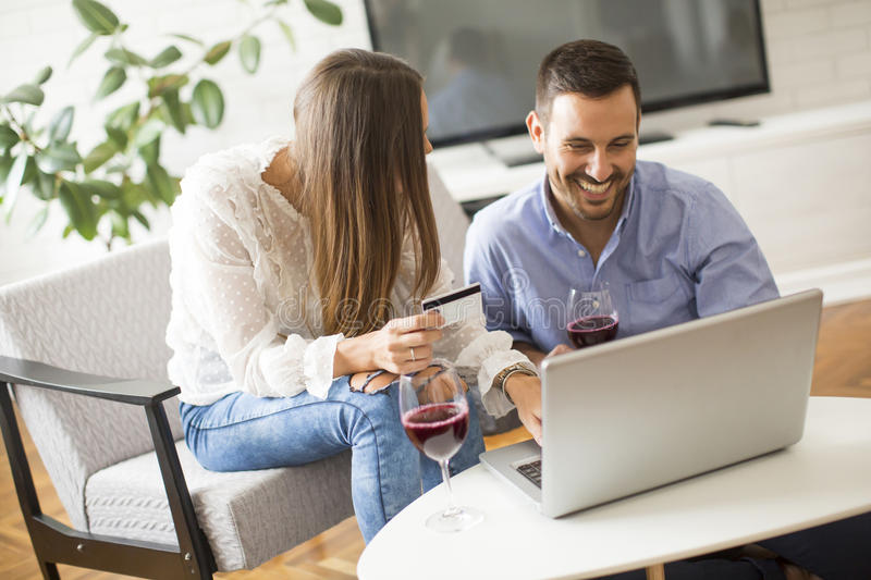 Cheerful couple searching internet and shopping online. In living room at home royalty free stock image