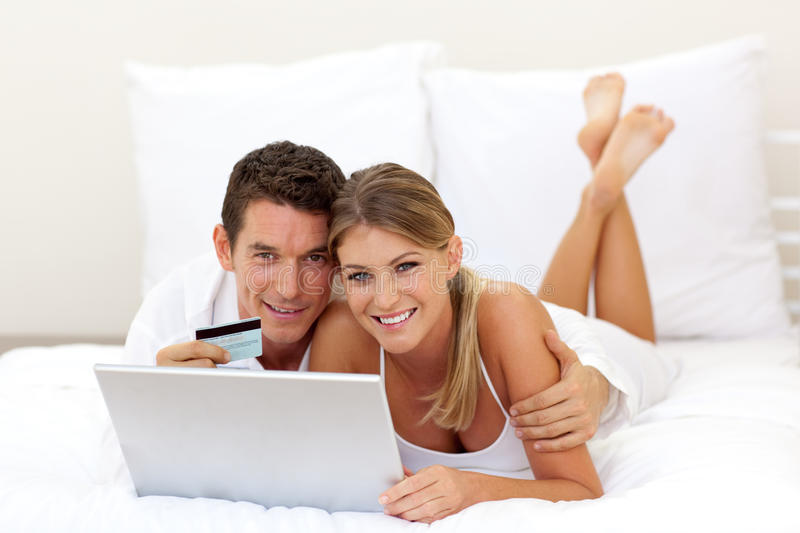 Cheerful couple shopping online. Lying on their bed stock images