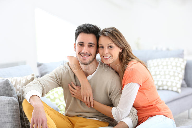 Cheerful couple sitting on sofa. Cheerful couple at home sitting in sofa stock photo