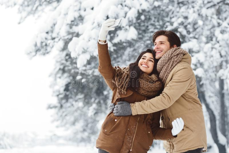 Cheerful Couple Taking Selfie On Smartphone Standing In Snowy Forest stock photography