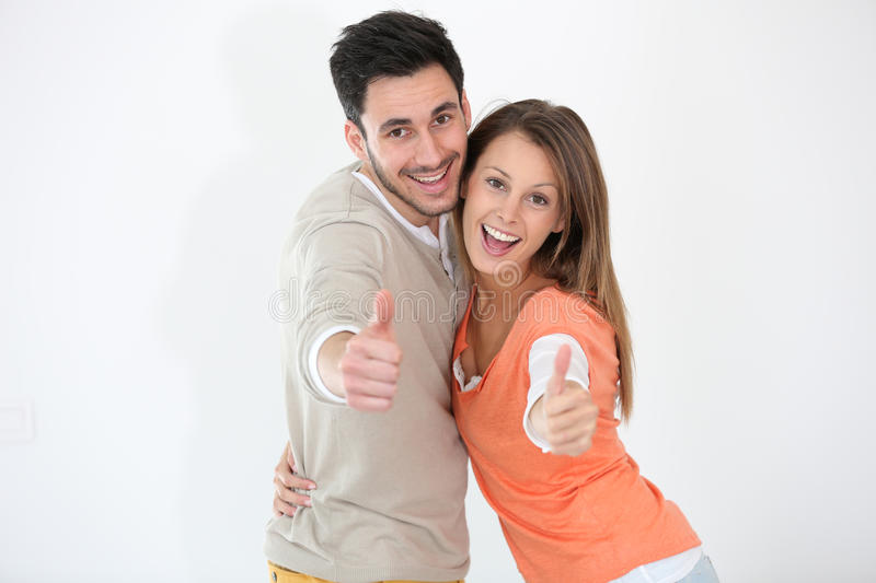 Cheerful couple with thumbs up. Cheerful couple showing thumbs up royalty free stock photography