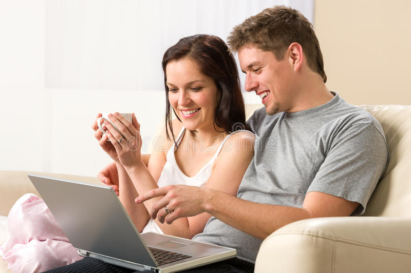Cheerful couple using laptop together royalty free stock images
