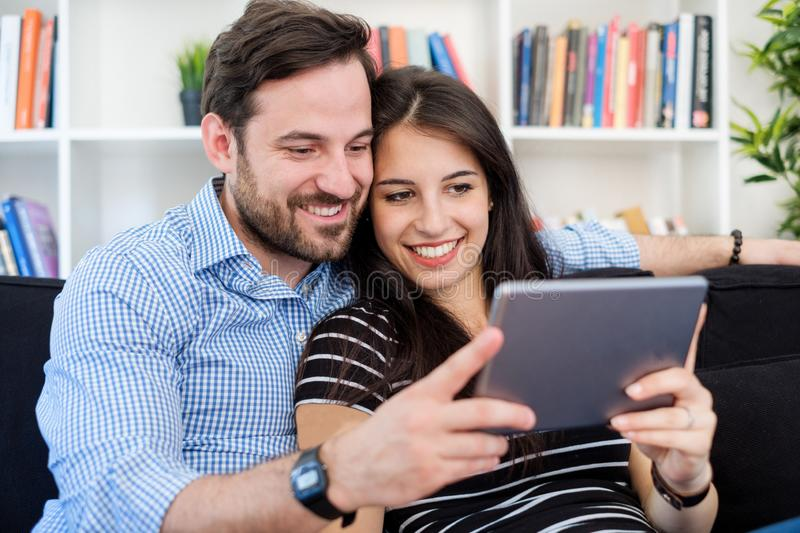 Cheerful couple using a tablet on line sitting in the living room at home stock photo