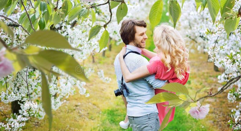 Cheerful couple walking among apple-trees stock image