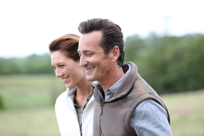 Cheerful couple walking in the fields royalty free stock images