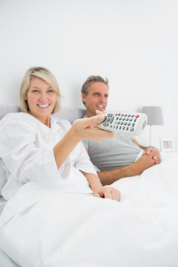 Download Cheerful Couple Watching Tv In Bed Stock Photo - Image: 32510472