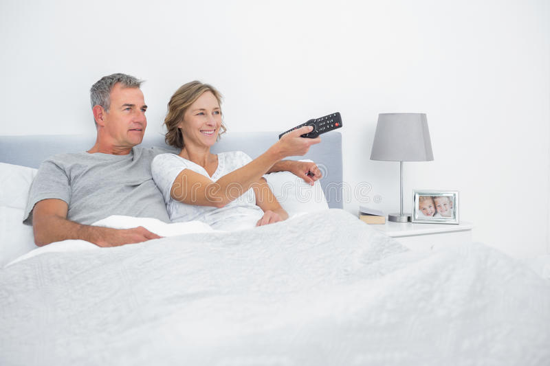 Cheerful couple watching tv in bed