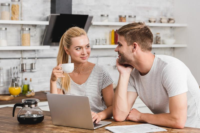 cheerful couple working together with laptop in morning and looking at each royalty free stock image