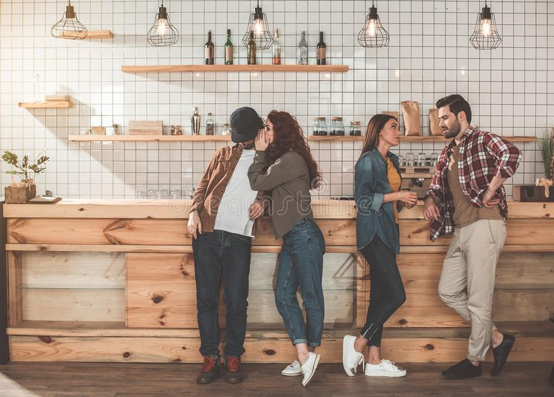 Cheerful couples having double date in cafe. Pretty girl is gossiping with her boyfriend secretly. Other couple is standing near and talking. Entertainment in royalty free stock photos
