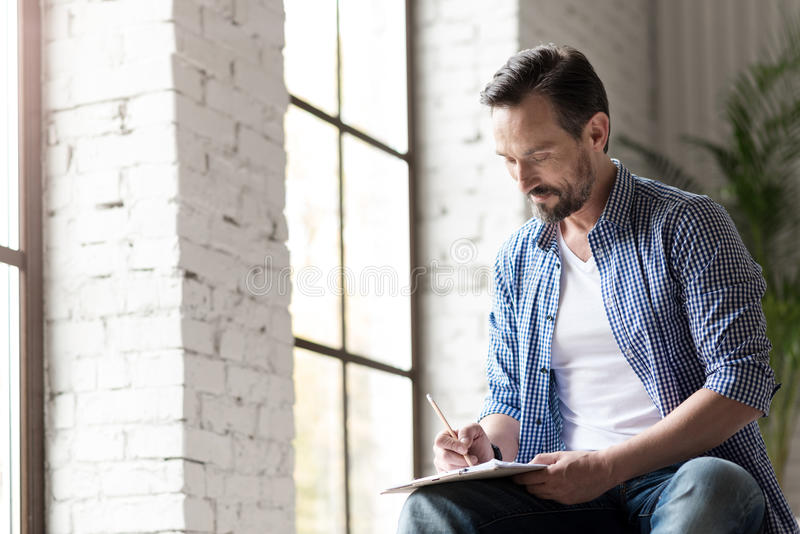 Cheerful creative man involved in drawing. Favourite hobby. Good looking delighted talented man sitting near the window and holding a pencil while drawing a stock images