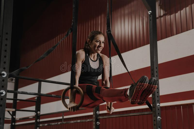 Cheerful crossfit woman doing abs exercises on gymnastic rings. Female athlete works on her abdomenal muscles during workouts at the gym royalty free stock photo