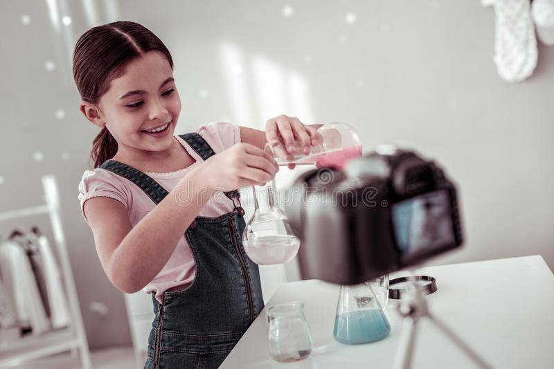 Cheerful curious girl being interested in chemistry stock image