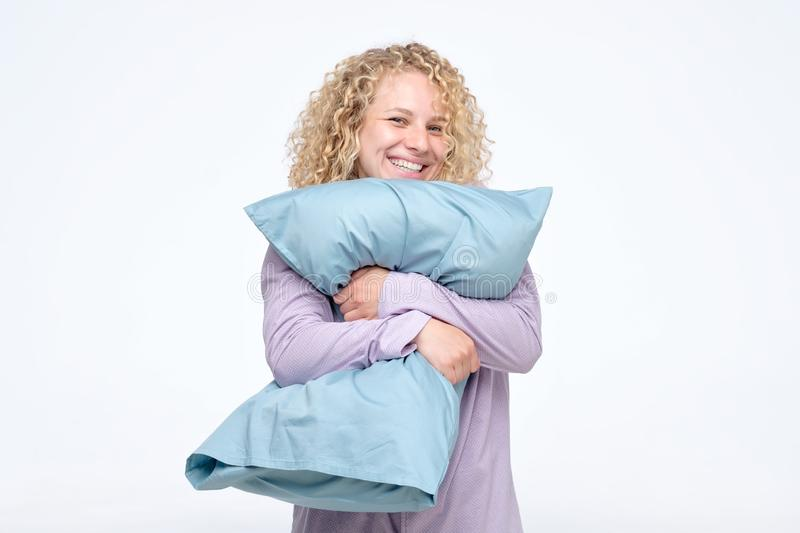 Cheerful curly blond woman in pajama hugging a pillow stock image