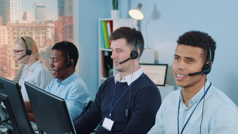 Cheerful customer support agent of mixed ethnicity talking on phone with a headset. He working in modern call center office stock photos